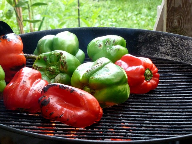 Green and red peppers roasting on the grill